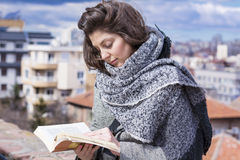 Young woman reading a book on a cityscape background Royalty Free Stock Photo