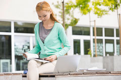 Young woman reading book at college campus Stock Images