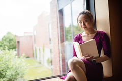 Young woman reading book in college Stock Photography