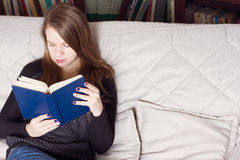 Young woman reading a book on couch Stock Image