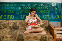 A young woman is reading a book on a couch Stock Photo