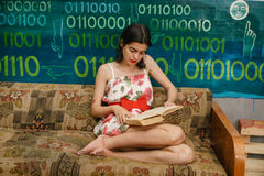 A young woman is reading a book on a couch. In a colorful room Royalty Free Stock Photo