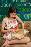 A young woman is reading a book on a couch. In a colorful room Stock Image