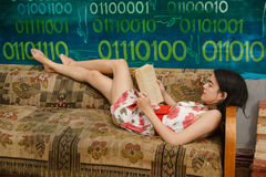 A young woman is reading a book on a couch. In a colorful room Stock Images