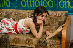 A young woman is reading a book on a couch Royalty Free Stock Photography