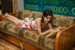 A young woman is reading a book on a couch. In a colorful room Royalty Free Stock Image