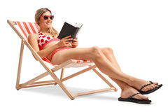 Young woman reading a book in a deck chair Stock Photo