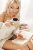 Young woman reading a book and drinking coffee. Young beautiful woman - blonde, wearing a warm knit short dress handmade, light - beige, reading a book with a Royalty Free Stock Photo