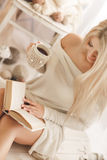 Young woman reading a book and drinking coffee. Young beautiful woman - blonde, wearing a warm knit short dress handmade, light - beige, reading a book with a Stock Images