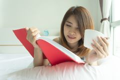 Young woman reading book drinking coffee on bed at home in the m royalty free stock photography
