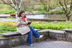 Young woman reading book and drinking coffee in spring park. Royalty Free Stock Image
