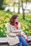 Young woman reading book and drinking coffee in spring park. Stock Photo