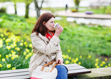 Young woman reading book and drinking coffee in spring park. Royalty Free Stock Photo