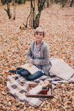 Young woman reading book and drinking tea in a forest Royalty Free Stock Photography