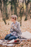 Young woman reading book and drinking tea in a forest Royalty Free Stock Images