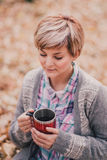 Young woman reading book and drinking tea in a forest Stock Photo