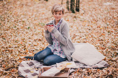 Young woman reading book and drinking tea in a forest Royalty Free Stock Photos