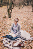 Young woman reading book and drinking tea in a forest Royalty Free Stock Photo