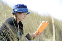 Young woman reading a book in the dunes Stock Image