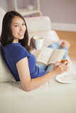 Young woman reading a book and eating pastry with coffee turning Royalty Free Stock Photos