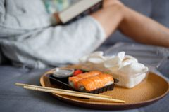 Young woman reading book and eating sushi stock photos