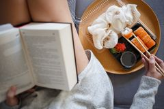 Young woman reading book and eating sushi royalty free stock photography