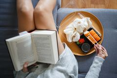 Young woman reading book and eating sushi royalty free stock images
