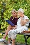 Young woman reading a book elderly woman. Young women reading a book elderly women in the park Royalty Free Stock Photos