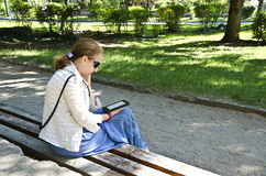Young woman reading book on electronic book-reader Royalty Free Stock Image