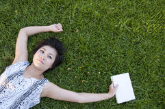 Young woman reading a book in the field Stock Photos