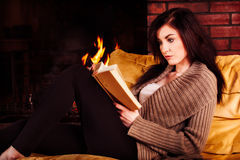 Young woman reading a book by fireplace royalty free stock photos