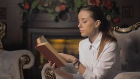 Young woman reading a book by fireplace. turns the pages stock video footage