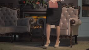 Young woman reading a book by fireplace. turns the pages stock video
