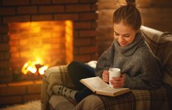 Young woman   reading a book by the fireplace on a winter evenin Royalty Free Stock Photos