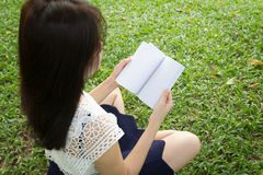 Young woman reading a book in garden Stock Images