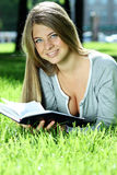 Young woman reading book on green grass Royalty Free Stock Image