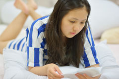 Young woman reading a book in her bed Royalty Free Stock Images