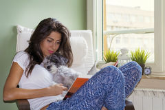 Young woman reading book  with her dog at home. Beautiful woman reading a book with her dog Royalty Free Stock Images