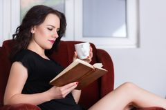 Young woman reading book and holding coffee cup stock image