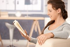Young woman reading book at home Royalty Free Stock Image