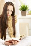 Young woman reading book at home Stock Photography