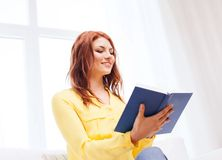 Young woman reading book at home Stock Images