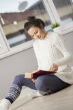 Young woman reading a book at home Royalty Free Stock Photos