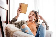 Young Woman Reading Book at Home with Happy Smiley Face and Relaxation Posture, Lay in Warm and Cozy House royalty free stock images