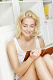 Young woman reading a book at home Royalty Free Stock Photography