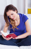 Young woman reading book at home Royalty Free Stock Images