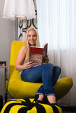Young woman reading a book in hotel room Royalty Free Stock Photography