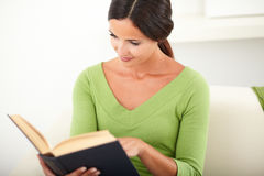 Young woman reading a book indoors Royalty Free Stock Photography