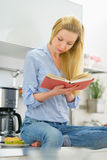Young woman reading book in kitchen Royalty Free Stock Photos