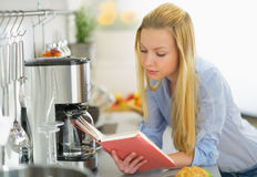 Young woman reading book in kitchen Royalty Free Stock Image